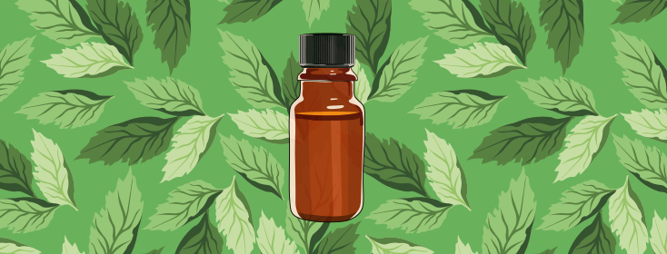 A bottle of essential oil against a background of mint leaves