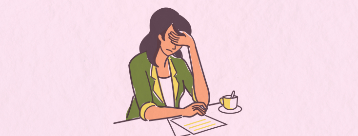 A woman sitting holding her head in her hand in front of a cup of coffee and some papers