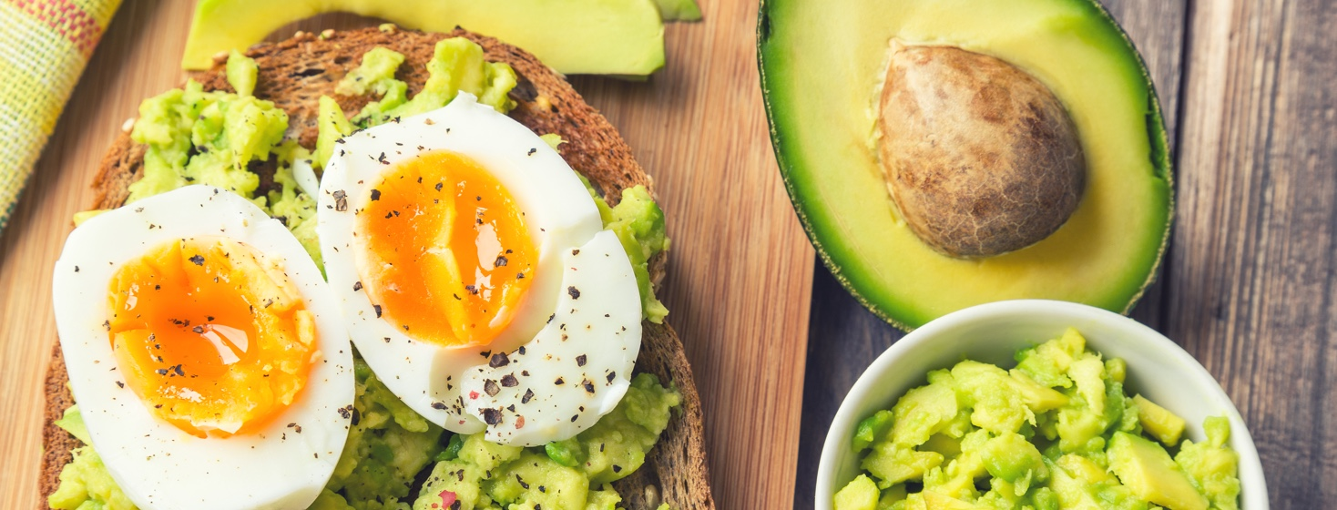 A soft boiled egg is on top of mashed avocado on a piece of toast with half an avocado and more mashed avocado to the right of it.