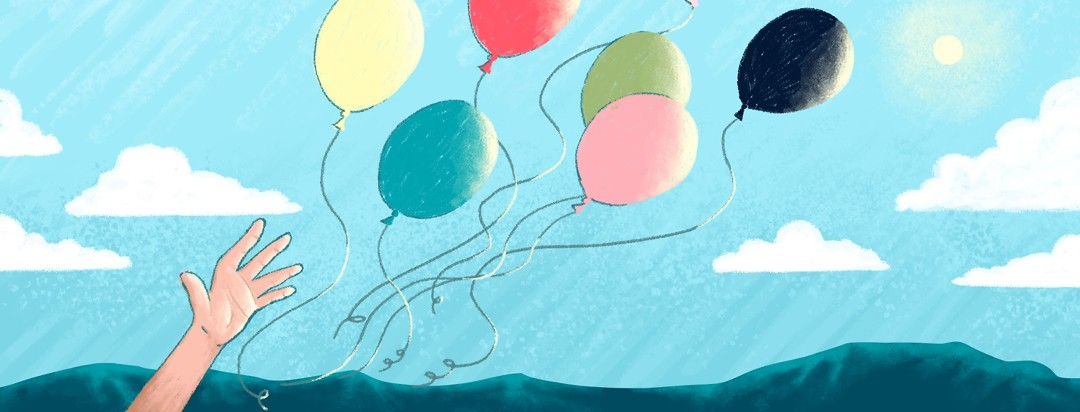 A hand releases a bunch of helium balloons into the air.