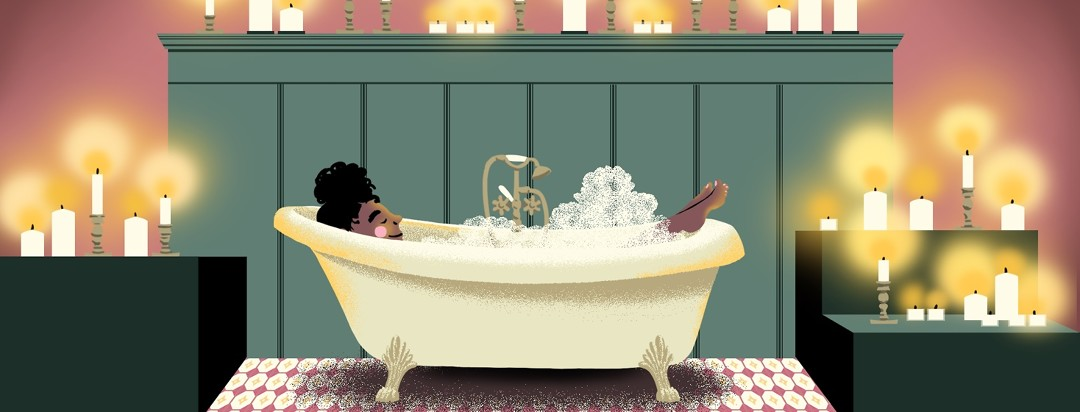 A woman relaxes in a bubble bath surrounded by lit candles.