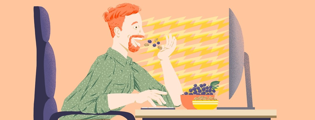 An energetic-looking man sits forward in an office chair facing a computer screen. One hand types on a keyboard, one tosses grapes and walnuts into his mouth.