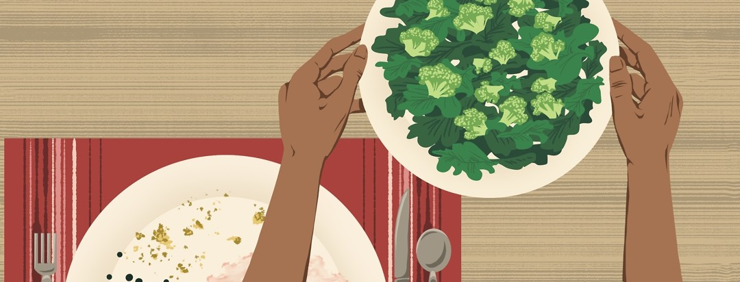 Two hands reach over a plate of finished food to bring forward a plate of salad.
