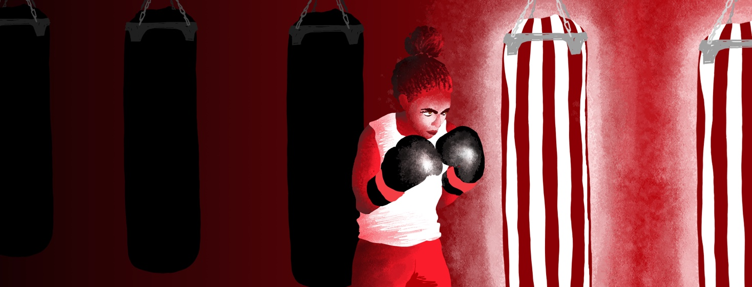 A female boxer determinately approaches a glowing punching bag.