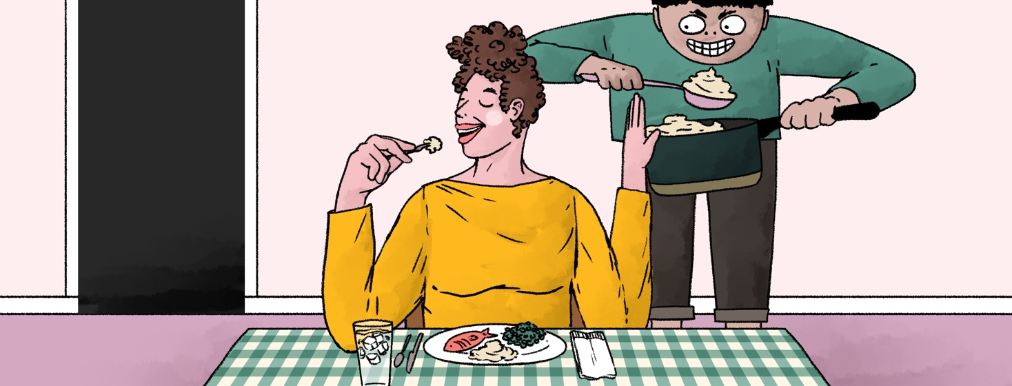 A woman sits at a dinner table smiling and putting her hand up at a menacing figure behind her that is trying to give her another serving of food.