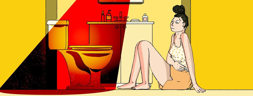 A woman sits uncomfortably on the bathroom floor with her hand over her stomach and staring warily at the toilet in front of her which is illuminated by an evil red light.