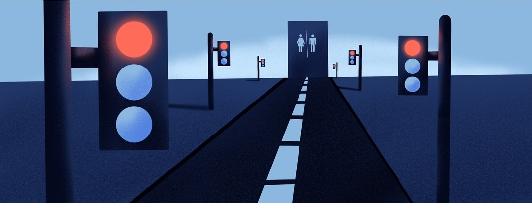 A long road with red lights all along the way stretches out into the distance, ending with a bathroom sign.