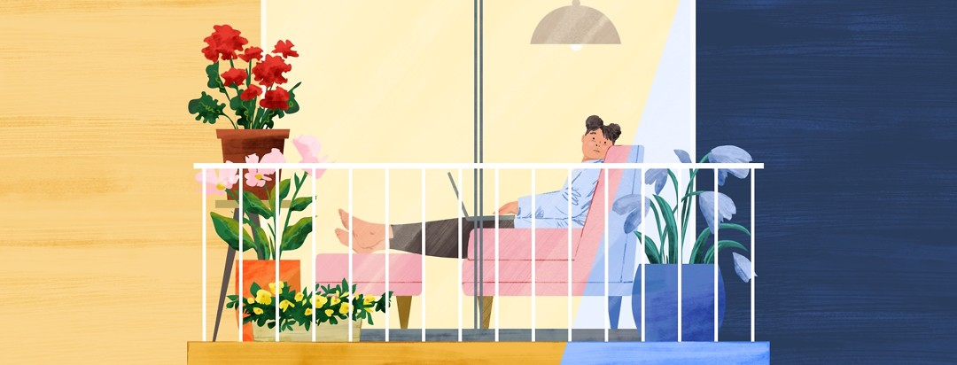 A woman sitting inside on a couch, wistfully looking out glass doors to her outdoor balcony, which is filled with potted plants.