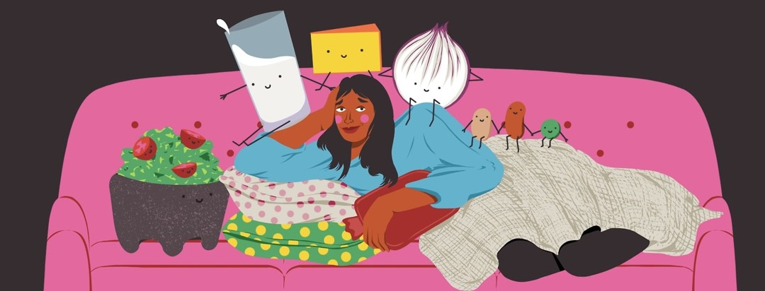A woman smiling but also looking a little guilty is cozied up onto a couch with a blanket over her, lots of pillows, and a hot water bottle on her stomach. She is surrounded by smiling foods like guacamole, a glass of milk, a hunk of cheese, a red onion, and beans and peas.