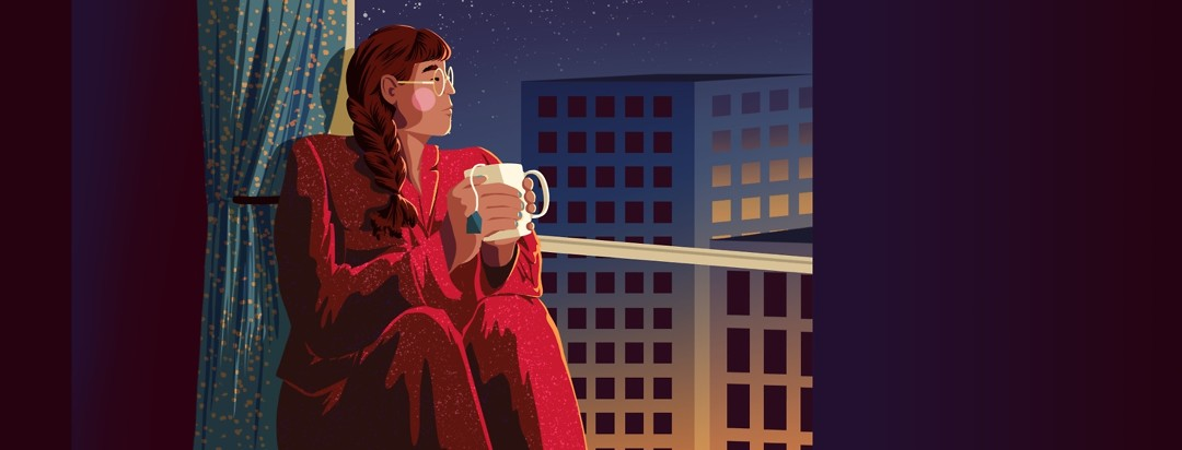 A woman in pajamas sits in a big window holding a cup of tea, looking out at the sunrise beginning to shine on the high-rise buildings in the city below.