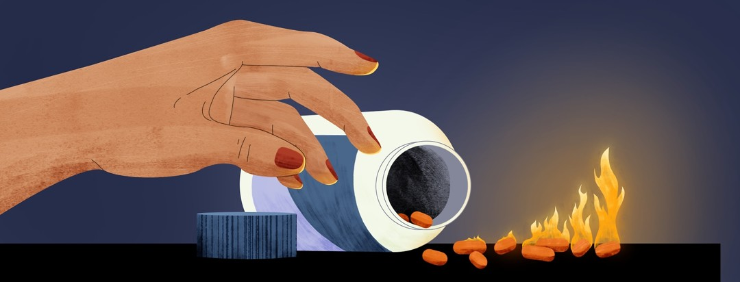 A hand reaches for an overturned, open bottle of pills. The pills that have spilled out are increasingly on fire.