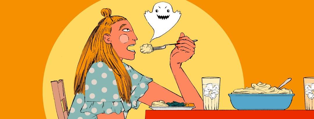 A woman sitting in front of a plate of food has her mouth open to received a bite but stops to look warily at an evil-looking ghost emerging from the food.