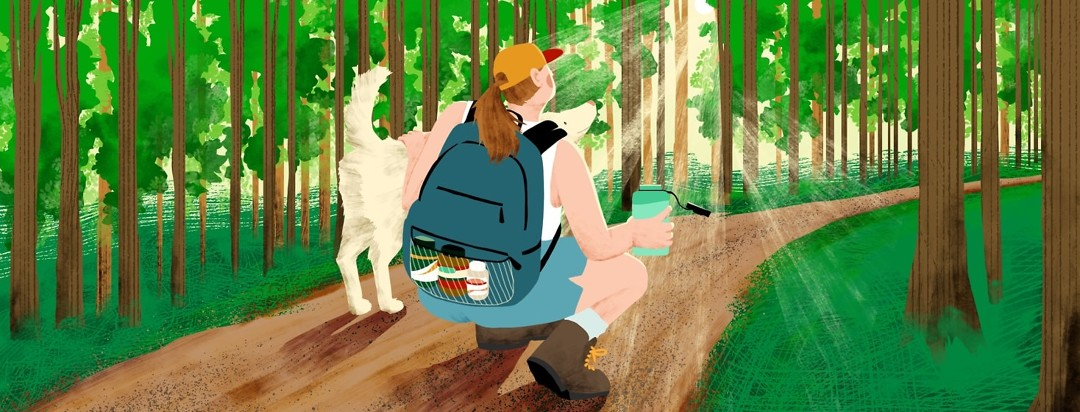 A woman crouches down on a nature path with one hand holding an open water bottle and the other on a dog. She is looking up at the sun that is coming through the trees around her. She is wearing a backpack with one pocket filled with bottles of supplements.
