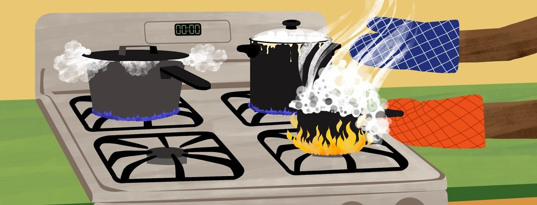 Two hands wearing oven mitts are taking an overflowing, boiling saucepan off the larger flames from a gas burner on a stove. On the two back burners, two larger pots look like they are bubbling up and almost overflowing as well.