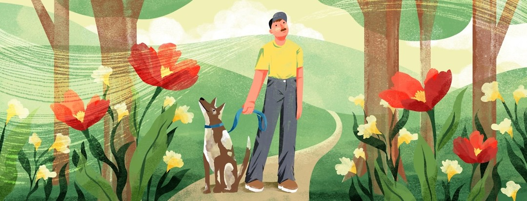 A man with a dog pauses on a nature path to look up into the trees and breathe in the air. Behind him are rolling hills and around him are large, bright flowers and grass.