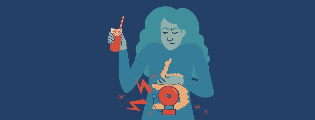 A frowning woman suppressing an alarm bell in her intestines as she drinks a milkshake.