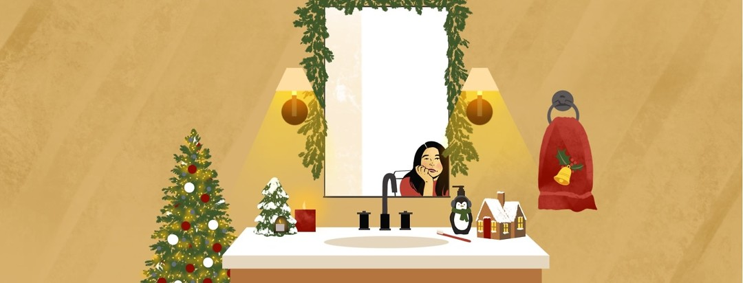 A bathroom decorated for Christmas features a garland-framed mirror that shows the reflection of a woman sitting on the toilet with a resigned, sad expression on her face.