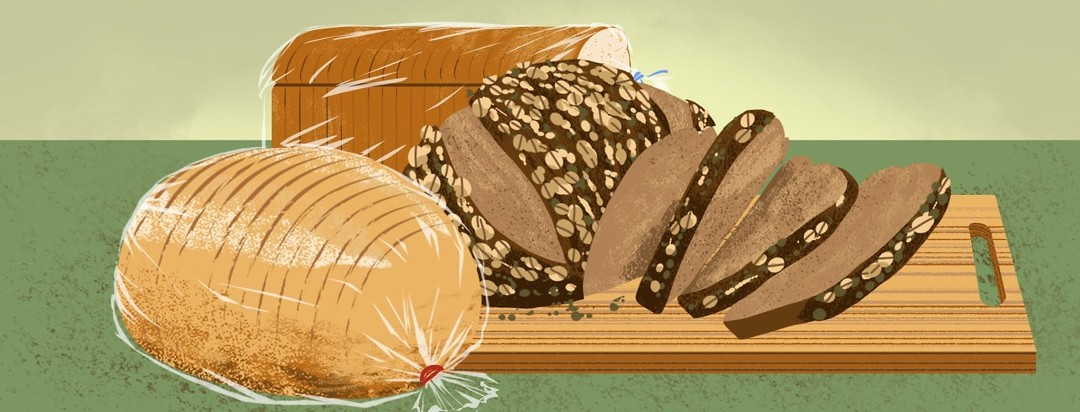 A variety of breads on a table and cutting board.