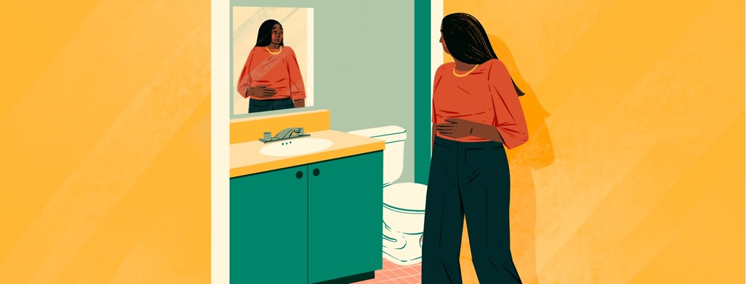 A woman is walking past the open door to a bathroom. She has one hand on her stomach and her reflection in the mirror shows her looking worried.