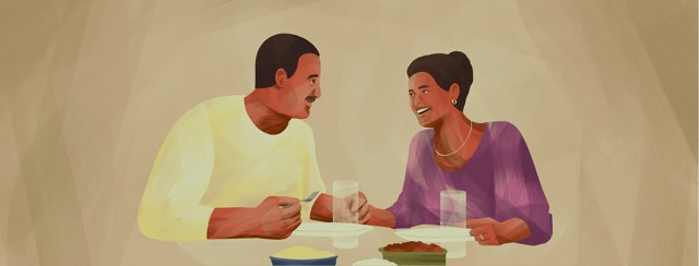 A couple happily eats dinner together.