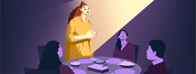 A woman stands up from a dinner table where she is sitting with three other people. She is speaking passionately and illuminated by a spotlight.