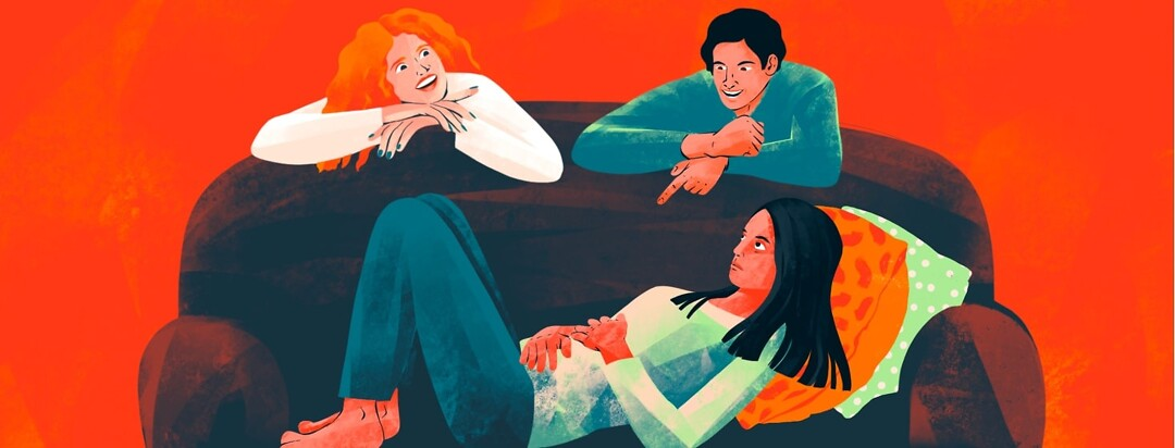 A woman looking miserable and holding her stomach is lying on her back on a couch while two smiling people lean over the back of the couch talking to her.