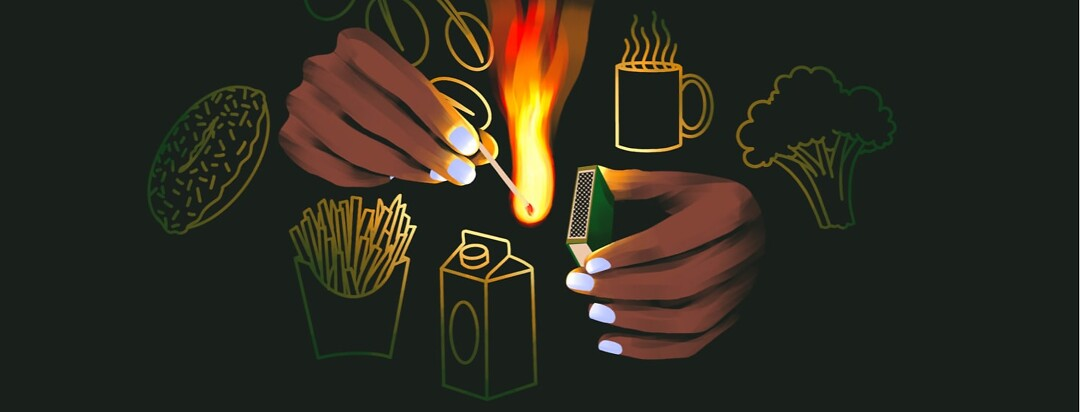alt=a hand strikes a match, illuminating various food items.