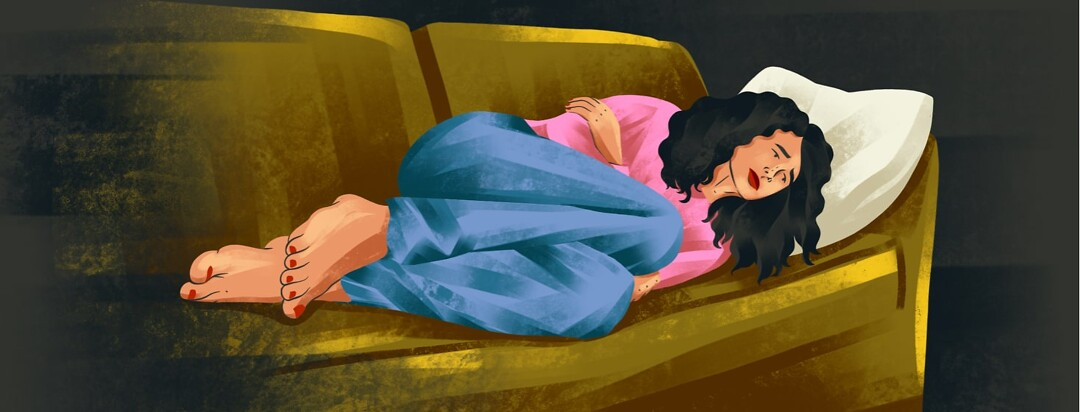 alt=a woman lies on her side on a couch, clutching her stomach in discomfort